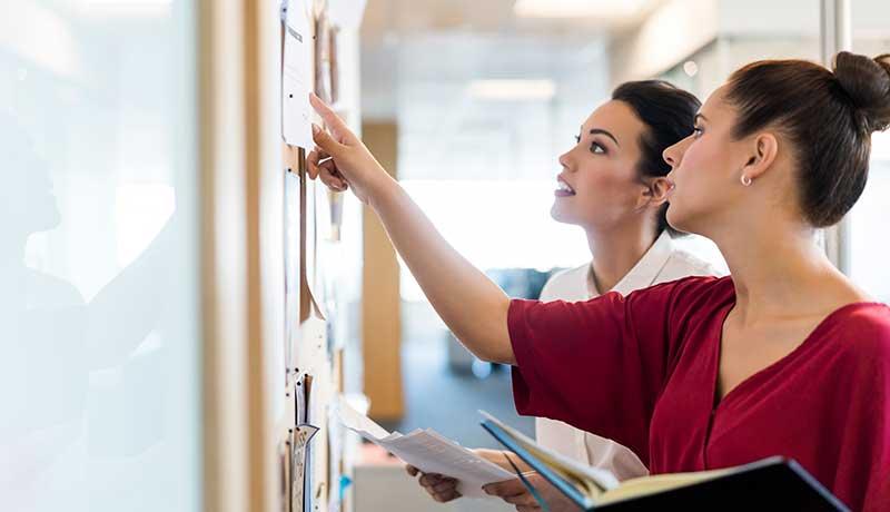Principal Looking at Action Board