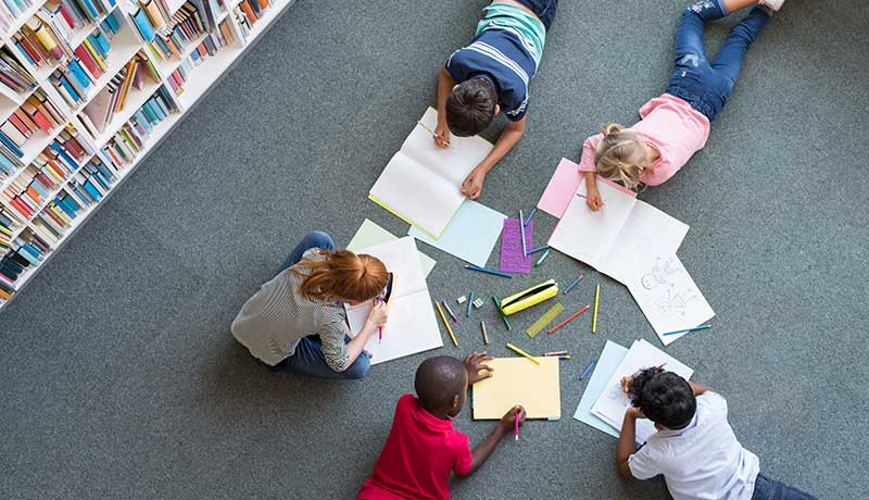 Aerial view of five students sitting and laying on the floor in a circle with their notebooks open and pencils out, engaged in collaborative peer learning.