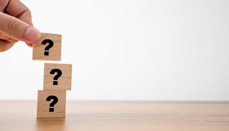 Three wooden blocks with the question mark symbol inside them, representing question-driven feedback.