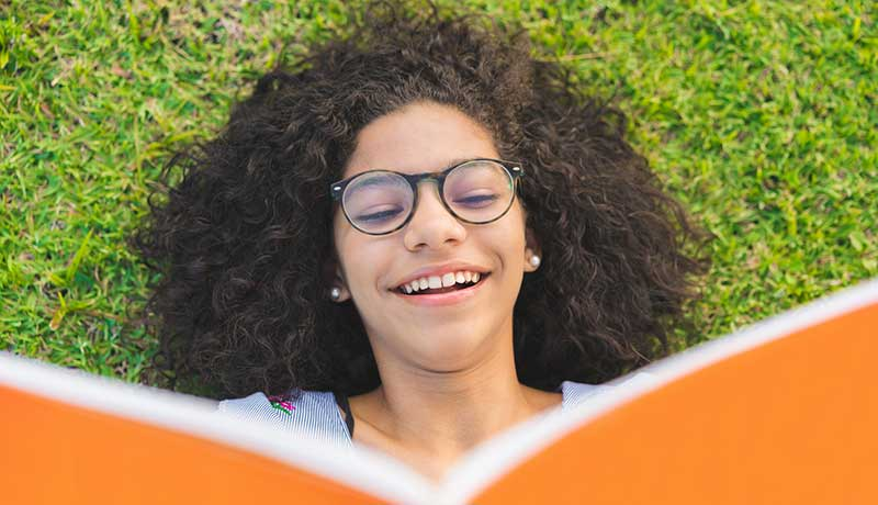 A girl wearing glasses lays in the grass on her back reading a book. Representative of a reluctant learner engaging in summer school best practices.