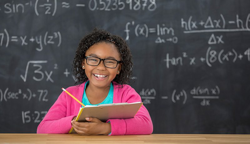 Elementary-aged Black female student smiling and holding a clipboard and pencil, seated in front of a classroom blackboard showing math problems. Symbolic of ESSER school funding allowable uses.