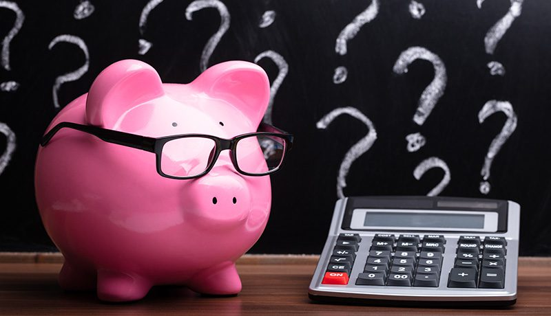 Piggy bank wearing glasses next to a calculator, with a classroom blackboard in the background showing question marks. Symbolic of questions about ESSER school funding.