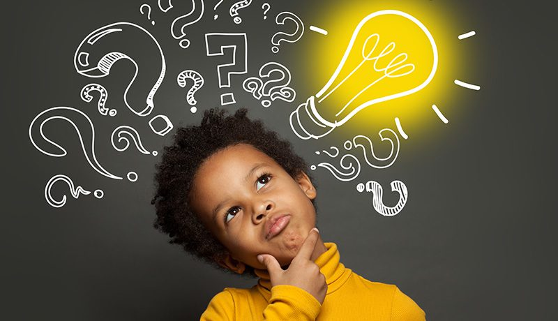Academic rigor and productive struggle. An elementary school-aged male student tilts his head up, thinking. A blackboard is in the background with drawings of question marks and a lightbulb.